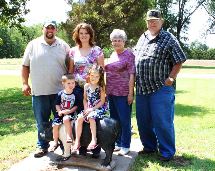 The Morris and Bohrn Families stop for a quick picture by the pig statue outside the farm.